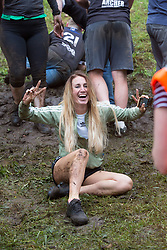 © Licensed to London News Pictures 26/05/2018, brockworth, Gloucester, UK. The annual cheese rolling race held at Coopers Hill, Brockworth outside Gloucester. Competitors race down the extremly steep slippery hill chasing a double Gloucester cheese, the winner of each race recieves the cheese as thier prize. Pictured here : A female competitor crosses the line of the ladies race - Photo Credit : Stephen Shepherd/LNP