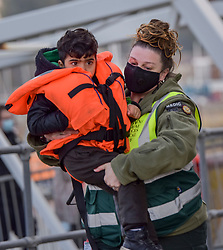© Licensed to London News Pictures. 14/04/2021. Dover, UK. A child migrant is helped ashore by a Border Force officer at Dover Harbour in Kent after crossing the English Channel. Home Secretary Priti Patel has pledged an overhaul of asylum seeker rules, with refugees having their claim assessed based on how they arrive in the UK. Photo credit: Stuart Brock/LNP