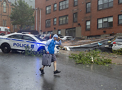 An unidentified man heads past part of an apartment roof that landed on several cars in Halifax as hurricane Dorian approaches on Saturday, September 7, 2019, Canada. Residents were evacuated from the building. Photo by Andrew Vaughan/CP/ABACAPRESS.COM