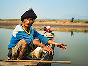 31 MARCH 2016 - NA SAK, LAMPANG, THAILAND: A fisherman sits in his canoe on a stream in the bottom of the Mae Chang Reservoir. This part of the reservoir is normally completely full of water. The Mae Chang Reservoir in Lampang province was created more than 30 years ago when the Chang River was dammed. Five villages along the river were relocated to hillsides above the river. For the first time since it was flooded, the reservoir is nearly empty and the ruins of the old villages are visible. Many people who remember the old villages are coming down to the ruins to visit them. This part of Thailand hasn't received significant rain in months and many irrigation canals and streams are running dry.    PHOTO BY JACK KURTZ