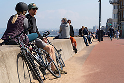Portobello, Scotland, UK. 25 April 2020. Views of people outdoors on Saturday afternoon on the beach and promenade at Portobello, Edinburgh. Good weather has brought more people outdoors walking and cycling. Police are patrolling in vehicles but not stopping because most people seem to be observing social distancing. People sitting on seawall . Iain Masterton/Alamy Live News