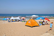 Holiday makers with tents camping on the shore at Achziv beach, Northern Israel