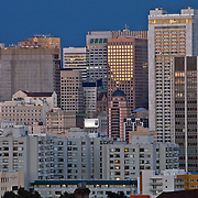 View of San Francisco skyline illuminated at dusk with zoom/telephoto lens from Alamo Square Park.