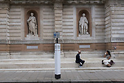 With a further 89 UK covid victims in the last 24hrs, bringing the total victims to 43,995 during the Coronavirus pandemic, pubs, restaurants, hairdressers and some art galleries such as here, at the Royal Academy, will open again on Saturday 4th July. Two Londoners sit and chat separated by 2 metres, according to the government's rules, as shown on many social distance notices around the capital, on 2nd July 2020, in London, England.