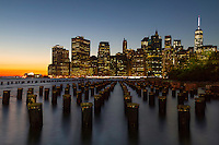 Limited Edition. Looking on from Brooklyn as the sun sets behind the monstrous city skyline of New York as the night lights begin to shine.