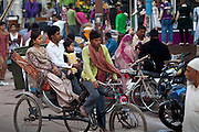 Young Indian family travel by rickshaw in crowded street scene in city of Varanasi, Benares, Northern India
