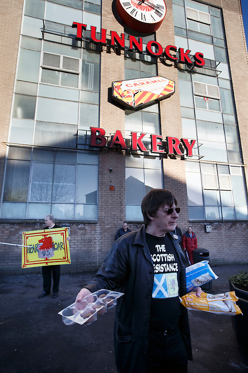 Members of the Scottish Resistance outside Tunnocks Factory in Uddingston to demonstrate their opposition to the removal of the lion rampant from the famous brand teacakes which are manufactured in the factory behind them. Giving out free Lee's products Tunnocks competitor. Picture Robert Perry 14th Jan 2016<br /> <br /> Must credit photo to Robert Perry<br /> FEE PAYABLE FOR REPRO USE<br /> FEE PAYABLE FOR ALL INTERNET USE<br /> www.robertperry.co.uk<br /> NB -This image is not to be distributed without the prior consent of the copyright holder.<br /> in using this image you agree to abide by terms and conditions as stated in this caption.<br /> All monies payable to Robert Perry<br /> <br /> (PLEASE DO NOT REMOVE THIS CAPTION)<br /> This image is intended for Editorial use (e.g. news). Any commercial or promotional use requires additional clearance. <br /> Copyright 2014 All rights protected.<br /> first use only<br /> contact details<br /> Robert Perry     <br /> 07702 631 477<br /> robertperryphotos@gmail.com<br /> no internet usage without prior consent.         <br /> Robert Perry reserves the right to pursue unauthorised use of this image . If you violate my intellectual property you may be liable for  damages, loss of income, and profits you derive from the use of this image.