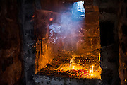 """19th November 2015, New Delhi, India.  Candles, incense sticks and an oil lamp burn at a shrine dedicated to Djinn worship in the ruins of Feroz Shah Kotla in New Delhi, India on the 19th November 2015<br /> <br /> PHOTOGRAPH BY AND COPYRIGHT OF SIMON DE TREY-WHITE a photographer in delhi<br /> + 91 98103 99809. Email: simon@simondetreywhite.com<br /> <br /> People have been coming to Firoz Shah Kotla to pray to and leave written notes and offerings for Djinns in the hopes of getting wishes granted since the late 1970's. Jinn, jann or djinn are supernatural creatures in Islamic mythology as well as pre-Islamic Arabian mythology. They are mentioned frequently in the Quran  and other Islamic texts and inhabit an unseen world called Djinnestan. In Islamic theology jinn are said to be creatures with free will, made from smokeless fire by Allah as humans were made of clay, among other things. According to the Quran, jinn have free will, and Iblīs abused this freedom in front of Allah by refusing to bow to Adam when Allah ordered angels and jinn to do so. For disobeying Allah, Iblīs was expelled from Paradise and called """"Shayṭān"""" (Satan).They are usually invisible to humans, but humans do appear clearly to jinn, as they can possess them. Like humans, jinn will also be judged on the Day of Judgment and will be sent to Paradise or Hell according to their deeds. Feroz Shah Tughlaq (r. 1351–88), the Sultan of Delhi, established the fortified city of Ferozabad in 1354, as the new capital of the Delhi Sultanate, and included in it the site of the present Feroz Shah Kotla. Kotla literally means fortress or citadel."""