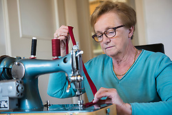 Old woman sewing on a machine