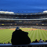 A panoramic view of the Yankees Stadium as a couple embrace during a night game between the New York Yankees V Baltimore Orioles Baseball game at Yankee Stadium, The Bronx, New York. 30th April 2012. Photo Tim Clayton