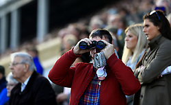 A racegoer looks through binoculars during day two of the Showcase at Cheltenham Racecourse