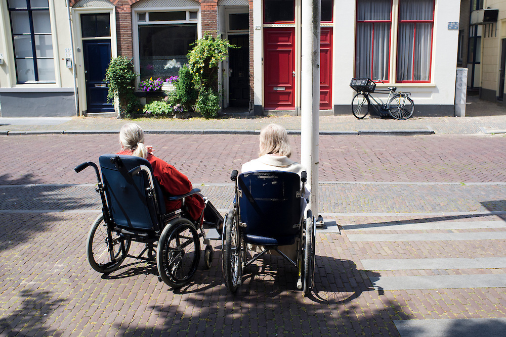 Twee oudere vrouwen wachten in een rolstoel op de taxi.<br /> <br /> Two elder women are waiting in their wheelchair for a taxi.