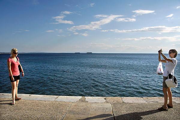 Griekenland, Thessaloniki, 11-6-2011Straatbeeld van deze stad in Noord Griekenland. Het is de tweede stad van het land. Twee toeristen maken een foto van elkaar. Schepen op de achtergrond.Griekenland is zwaar getroffen door het wanbeleid van voorgaande regeringen op financieel gebied. Foto: Flip Franssen