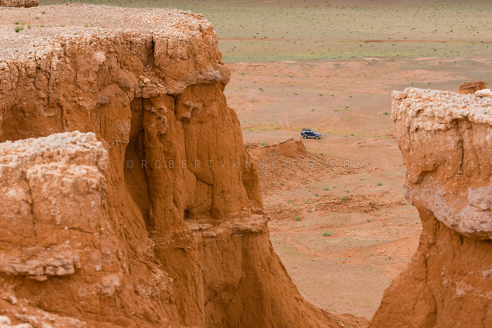 A jeep seen from the top of the Bayanzag Flaming Cliffs, Mongolia. Photo ©robertvansluis.com