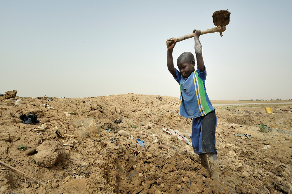 Mohamed Ag Aldjoumett, age 10, digs clay to make bricks for his family's home in Toya, a village in northern Mali near Timbuktu. The region was seized by Islamist fighters in 2012 and then liberated by French and Malian soldiers in early 2013. The Sahel region has been affected by a food crisis for years, often exacerbated by severe droughts.