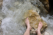 A pair of bare walker's feet enjoying the cooling nature of a mountain river in Italy.