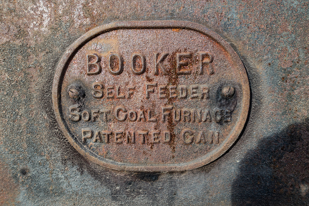 Rusting label identifying manufacturer is stamped on old self feeding soft coal furnace, made by Booker, and patented in Canada.