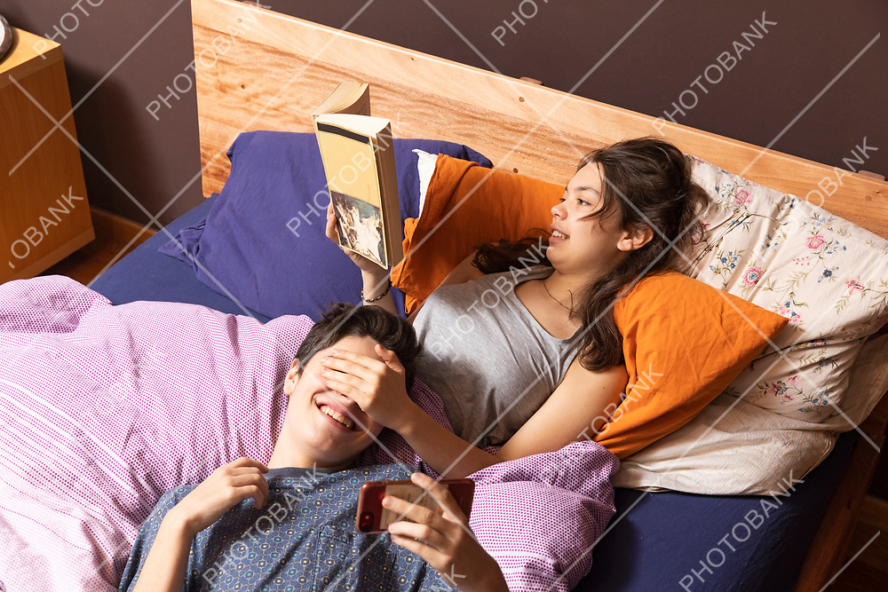 Young couple in bed. She reads a book while playing with him trying to look the phone