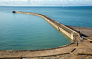 Large breakwater concrete groyne Newhaven, East Sussex, England. Sediment accumulation illustrates longshore drift.