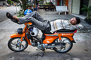 A man is sleeping on his motorbike in a street of Phnom Penh, Cambodia. Khmer people can be very creative in the way they rest.