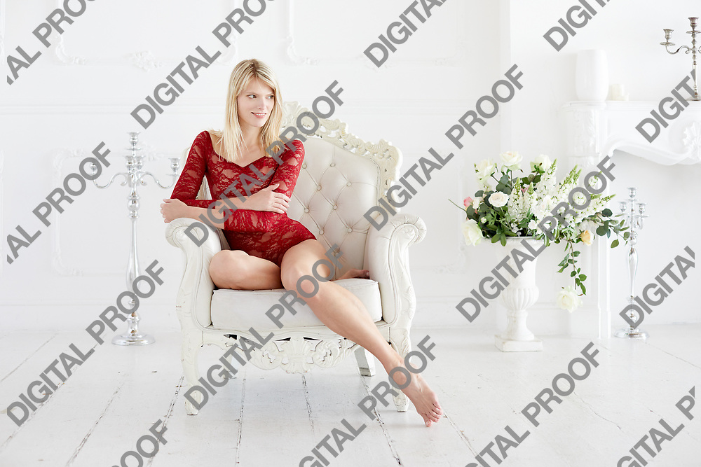 Happy woman in a red lace bodysuit and barefoot sitted in a sofa with looking into copy space in a white interior room.  Women boudoir concept.