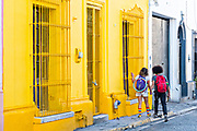 A couple walks past a brightly painted Spanish colonial style building in the Barrio Antiguo or Spanish Quarter neighborhood adjacent to the Macroplaza Grand Plaza in Monterrey, Nuevo Leon, Mexico.