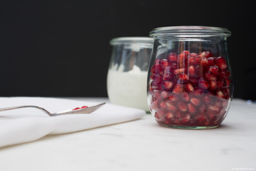 Front view of a glass container of pomegranate arils (seeds), and yogurt.  A few seeds rest on a spoon on a napkin.