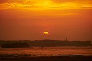 Loredo. Puesta de Sol en la playa de Loredo con la Bahia de Santander al fondo. Con el Faro de Mouro en primer térmico y en ultimo plano el faro de Cabo Mayor