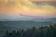 A DC-10 aircraft paints lines of fire retardant across a ridge after a lightning storm pummeled Northern California starting hundreds of wildfires across the region.