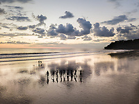 Aerial view of silhouettes of people dancing on beach at sunset, Costa Rica.