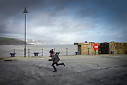 Folkestone, England, 22 feb 2020, Looking back at an image taken just before the European outbreak of Corona... Remember our open-mindedness, our freedom... Young boy running along the Folkestone Harbour Arm