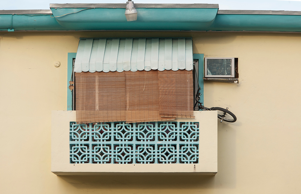 A Miami Modern masonry balcony in South Beach -- with an air-conditioner and bicycle