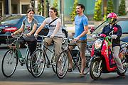 01 APRIL 2013 - BANGKOK, THAILAND:    Tim and Amy Hupe and Molly Evans navigate Bangkok's chaotic streets on bikes. PHOTO BY JACK KURTZ