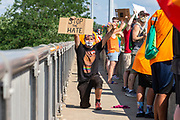 """Issac holds a sign reading """"stop the hate"""" while kneeling during the Milton Pride Rally in Milton, Pennsylvania on August 8, 2020. The I Am Alliance organized the event after a local grocery store posted an anti-mask sign which blamed the LGBTQ community for spreading COVID-19."""