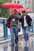 Tourists with umbrellas walking and taking photographs on Tower Bridge during rain and wet weather in London, England on August 10, 2018