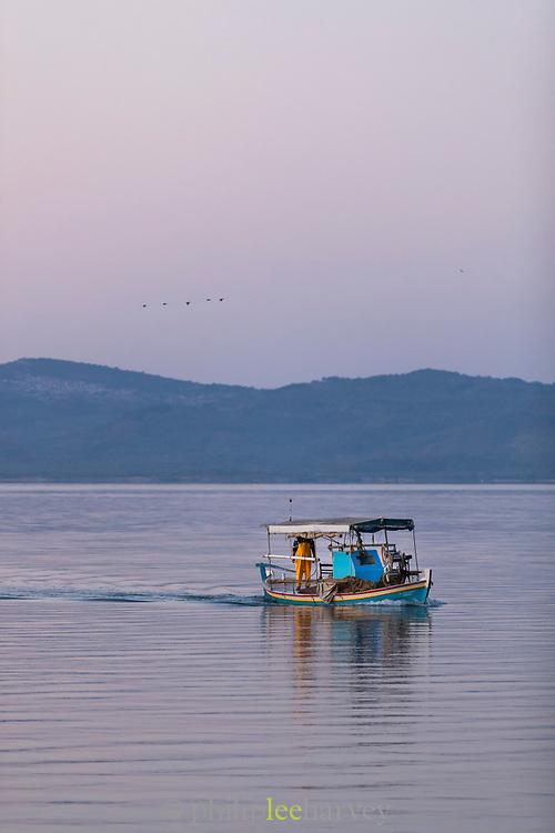 Fisherman on boat in harbor at dawn, Skala Kallonis, Lesbos, Greece