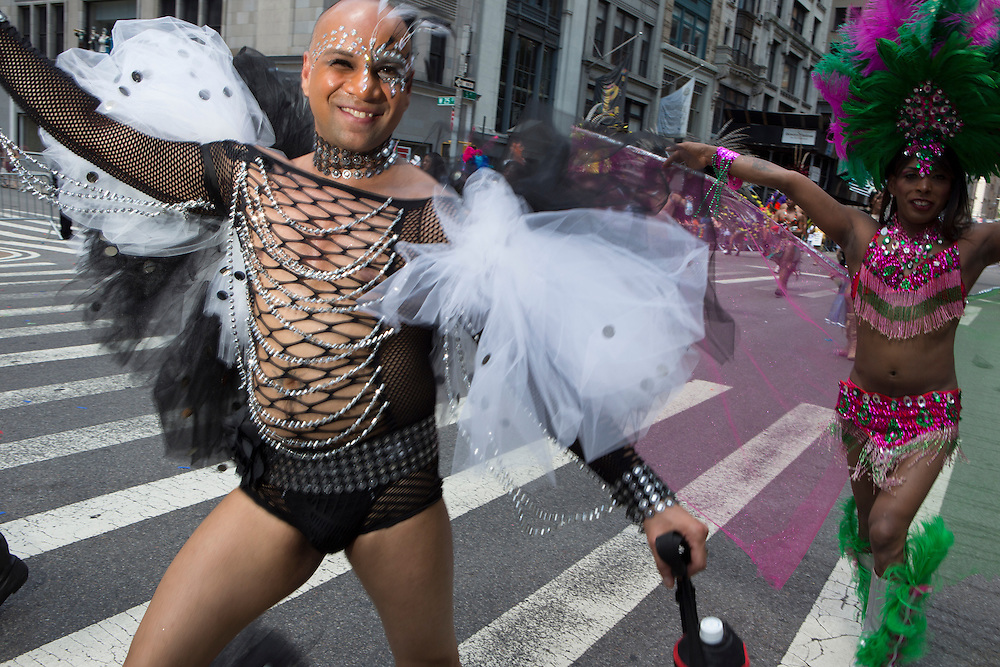 A man wears a black lace body suit with white tulle wings.
