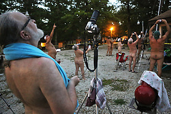 Members and guests of the Forty Acre Club, a nudist club near Lonedell, took pictures of the eclipse as it neared totality. Three hundred and fifty four sun worshippers were in attendance for the weekend festivities. One couple traveled from France to be at the club, while another came from London. The man in the foreground, Jim Caddell, 63, from Dallas, came with his wife to view the eclipse. He said that this club is the only nudist club within the area of the eclipse totality that he knew of. Then, he and his wife plan to go on to Burning Man festival in Nevada. Photo by J.B. Forbes/St. Louis Post-Dispatch/TNS/ABACAPRESS.COM
