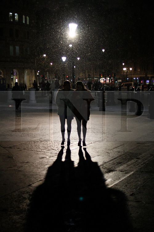 © licensed to London News Pictures. London, UK 04/02/2012. Two girls walking in Trafalgar Square as London is hit by snow today (04/02/12). Photo credit: James Gourley/LNP