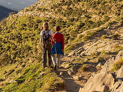Boy and girl walking on single trail towards the top of Txindoki
