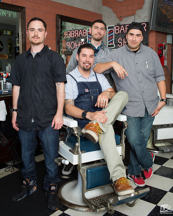 From left to right, Garrison Finks, owner Alex Franco (sitting), Chris Ramsour, and Fabi Gomez pose for a portrait around one of four classic barber chairs at Alex's Classic Barber Shop & Shaves in Fremont, California, on April 9, 2014. (Stan Olszewski/SOSKIphoto)