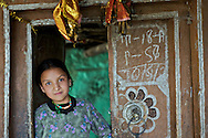 A girl stands in the doorway of her village home in the community of Ropa, Himachal Pradesh, India