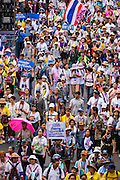 """09 MAY 2014 - BANGKOK, THAILAND:  Thai anti-government protestors march through the streets of Bangkok. Thousands of Thai anti-government protestors took to the streets of Bangkok Friday to start their """"final push"""" to bring the popularly elected of government of Yingluck Shinawatra. Yingluck has already been forced out by a recent court ruling that forced her to resign and she is facing indictment by the National Anti Corruption Commission of Thailand for alleged improprieties related to a government rice price support scheme. The protestors Friday were marching to demand that she not be allowed to return to politics. The courts have not banned her party, Pheu Thai, which has formed an interim caretaker government to govern until elections expected in July, 2014. Suthep Thaugsuban, secretary-general of the People's Democratic Reform Committee (PDRC),  said the president of the Supreme Court and the new senate speaker, who would be selected Friday, should set up an """"interim people's government and legislative assembly."""" He went onto say that if they didn't, he would.    PHOTO BY JACK KURTZ"""