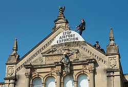 © Licensed to London News Pictures;20/07/2021; Weston-super-Mare, UK. Campaigners against the expansion of Bristol Airport protest at Weston-super-Mare Town Hall on the first day of the planning appeal into the proposal to expand the airport. The protests include two activists who have climbed on the roof of the Town Hall and hung a banner and an effigy of Bristol Airport's CEO Dave Lees. North Somerset councillors rejected the expansion proposals in 2020 and now planning appeal has been launched by Bristol Airport. The expansion of Bristol Airport would allow an extra 23,800 flights a year to new destinations. Campaigners including Bristol Airport Action Network (BAAN) and Extinction Rebellion say that science shows airports should not be expanded due to the effects of climate change which are extreme and damaging for our planet, and for children. They also say for an airport expansion to be approved in the same year when the UK is hosting the COP26 climate summit would be a national and international disgrace. Photo credit: Simon Chapman/LNP.