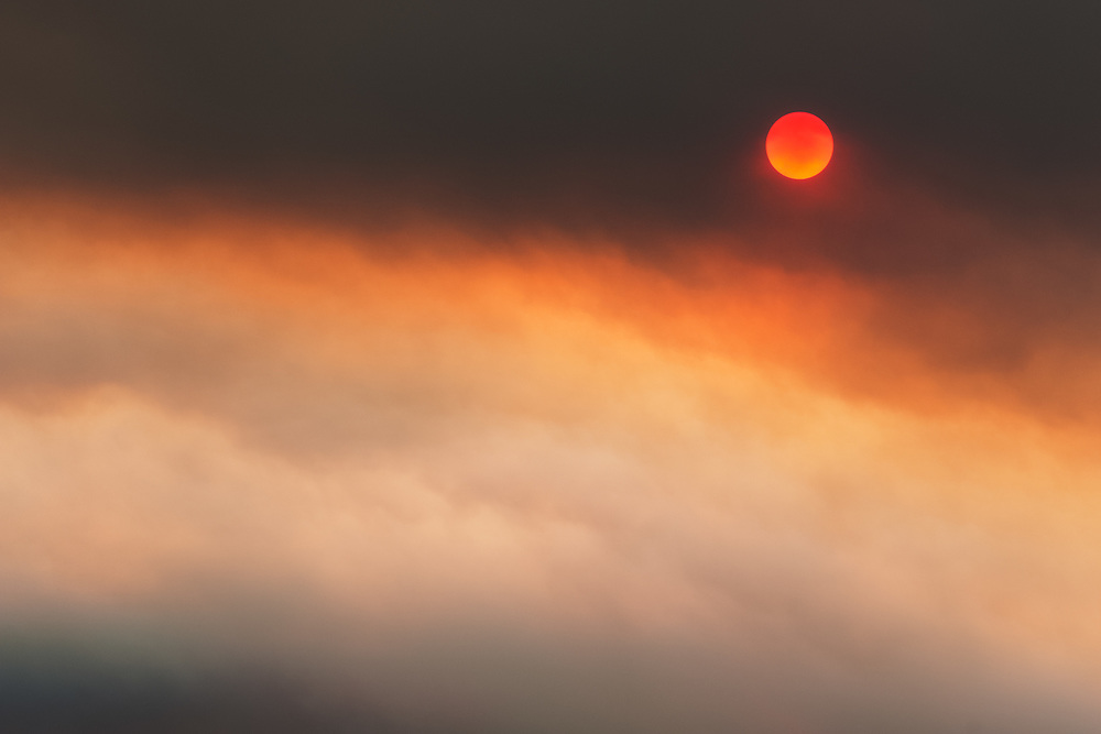 A red sun is seen through thick smoke during a controlled burn in the Black Hills.