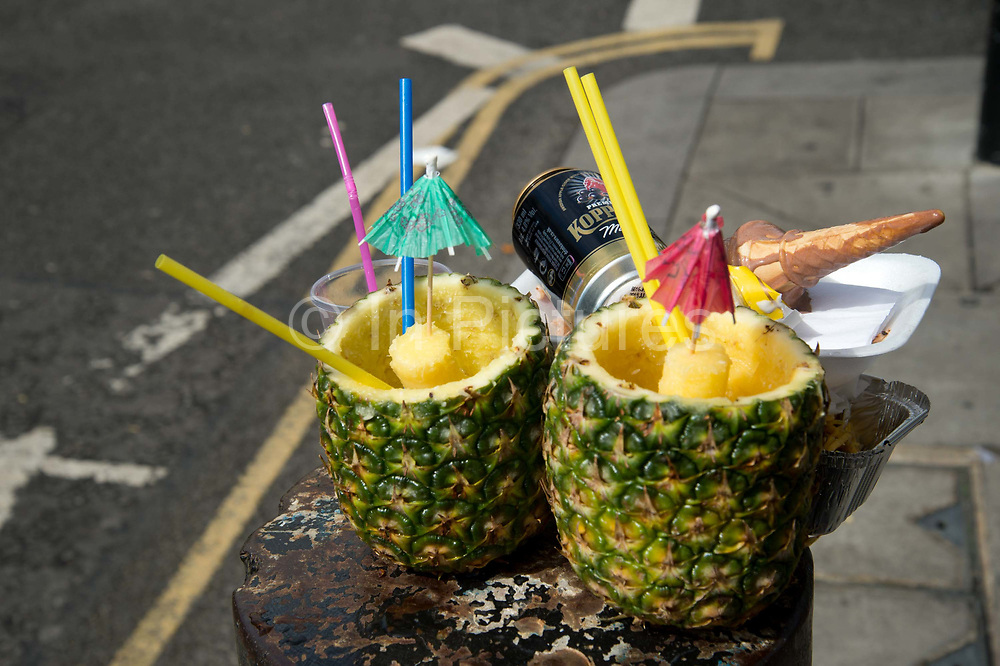 Notting Hill Carnival 2016 Childrens Day. Two discarded pineapples which had been filled with rum punch, alongside an empty beer can and icecream.