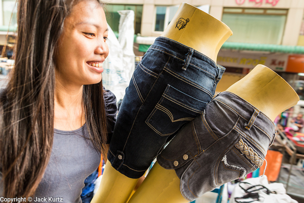 06 JUNE 2013 - BANGKOK, THAILAND:     A blue jeans vendor carries jeans mannequins through Bobae Market in Bangkok. Bobae Market is a 30 year old market famous for fashion wholesale and is now very popular with exporters from around the world. Bobae Tower is next to the market and  advertises itself as having 1,300 stalls under one roof and claims to be the largest garment wholesale center in Thailand.       PHOTO BY JACK KURTZ