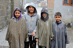 Kashmiri young boys poses for the picture during the snowfall in Srinagar, the summer capital of Indian controlled Kashmir. Kashmir witnessed its first snowfall.