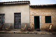 Rocking chairs lined up on the sidewalk outside a home in Remedios, Cuba Thursday July 17, 2008.