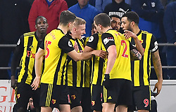 Watford's Gerard Deulofeu (hidden) celebrates scoring his side's first goal of the game with team-mates during the Premier League match at the Cardiff City Stadium.